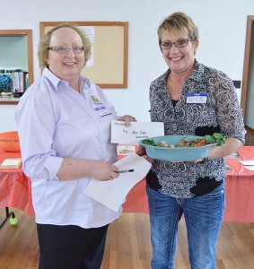 Connie Murphy presents Rose Schlater with the prize for top main dish recipe. Photo courtesy the Sidney Daily News and photographer Luke Gronneberg.