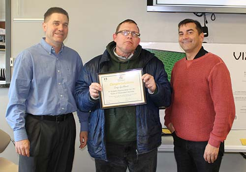 Craig Quellhorst receives a 15-year service award from Devon Beer and Phil Gilardi